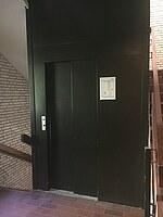 Das Bild zeigt einen Aufzug älteren Baujahres, der in einem Treppenhaus integriert ist.
