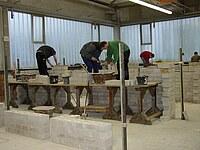 Mehrere Schüler arbeiten auf einem Bockgerüst und erstellen ein Mauerwerk