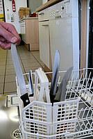 Hier ist zu sehen, wie scharfe Küchenmesser Messer mit de Klinge nach oben in den Spülmaschinenkorb eingeräumt sind.