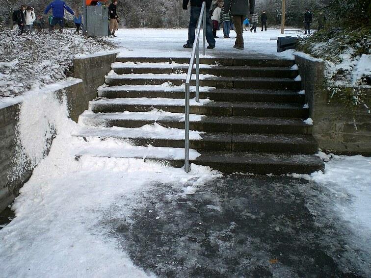 Eine Treppe auf dem Schulgelände ist nur auf einer Seite geräumt. Die andere Seite ist im Schnee versunken.