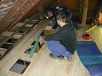Dieses Bild zeigt zwei Schüler beim Verlegen von Rauhspundbretter als Bodenbelag.