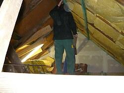 Hier ist das Anbringen von Glaswolle zwischen den Dachsparren zu sehen.