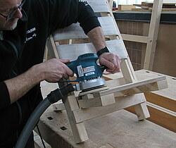Hier wird die Holzoberfläche eines Stuhles mit einem Excenterschleifer maschinell geschliffen.