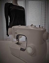 Nähmaschine mit Schneiderbüste im Hintergrund