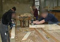 Das Bild zeigt Schüler bei der Endbearbeitung eines Kantholzrahmens mit einem Exenterschleifer und einer Oberfräse.