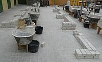 Das Bild zeigt mehrere eingerichtete Maurerarbeitsplätze. Gut zu erkennen sind hier die Abstände zu dem zu erstellenden Mauerwerk sowie die Verkehrswege zum Transportieren des Materials, wie z. B. Steine und Mörtel.
